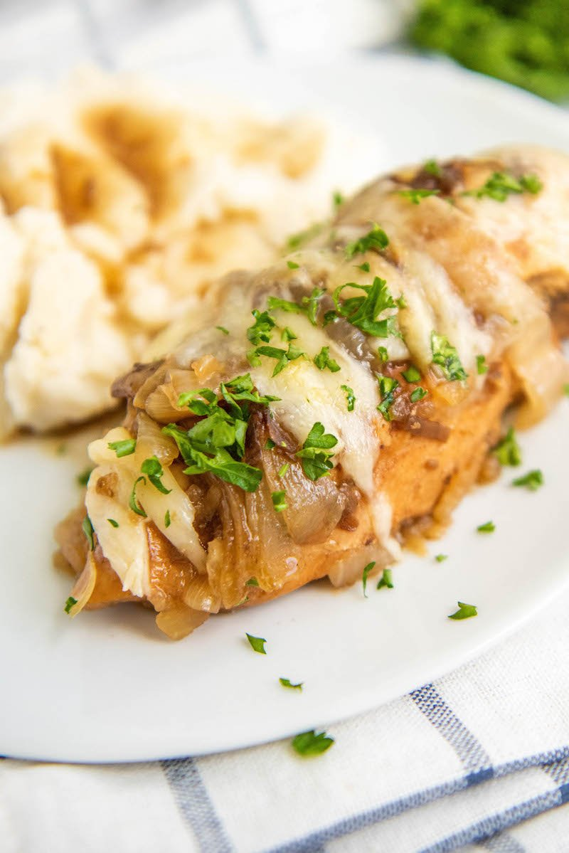 Crockpot French Onion Chicken on a white plate with mashed potatoes and parsley on top.