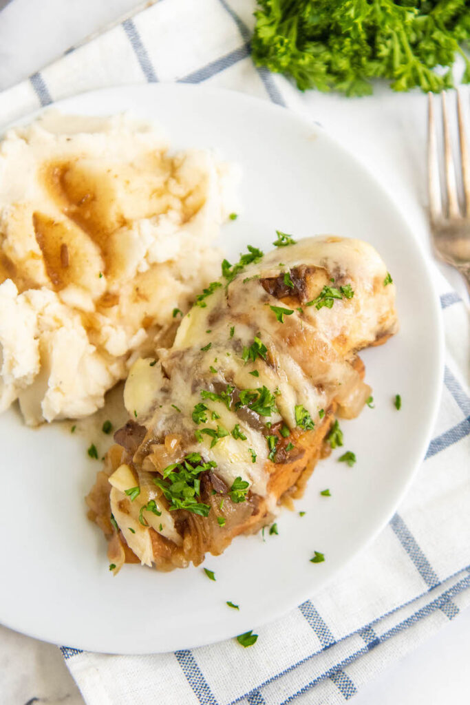 Chicken with melted cheese and french onions on top on a white plate with mashed potatoes.