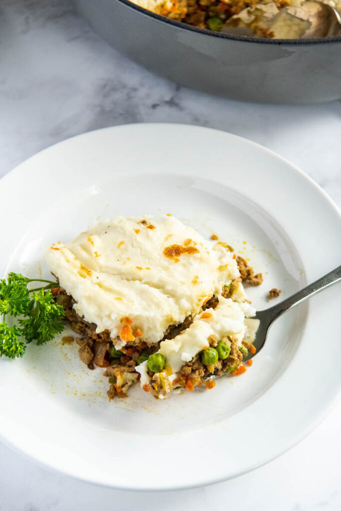 Shepherd's pie on a white plate with a fork and parsley.