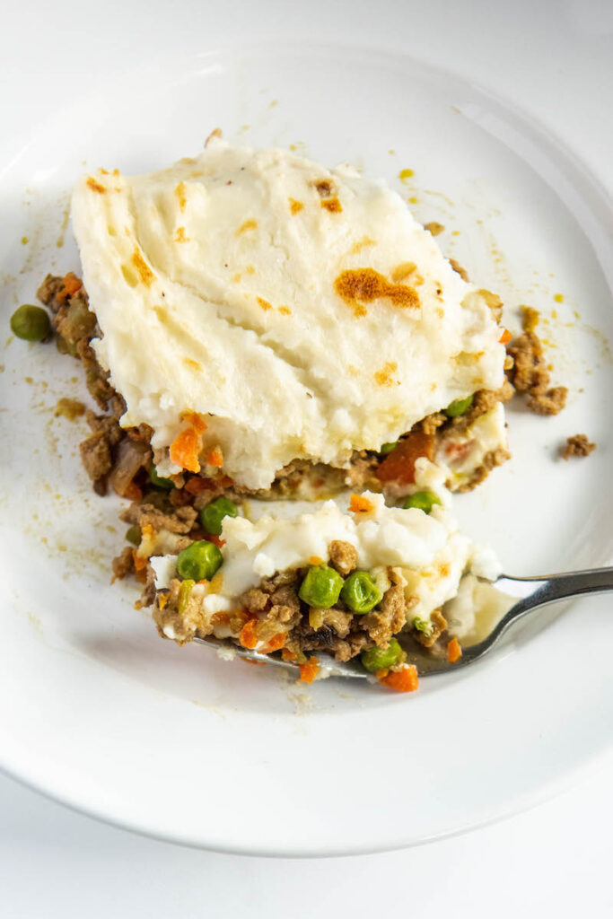 Shepherd's Pie on a white plate with a fork taking a bite out of it.
