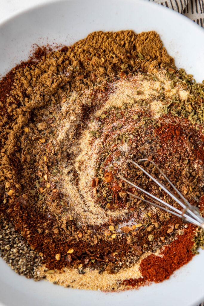 Taco seasonings mixed together in a  bowl with a whisk.