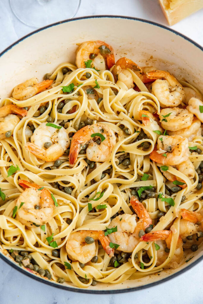 Shrimp Scampi tossed over pasta in a large pan.