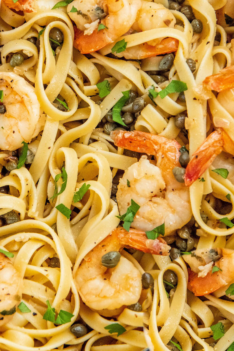 Up close image of Shrimp Scampi tossed with pasta and fresh parsley.