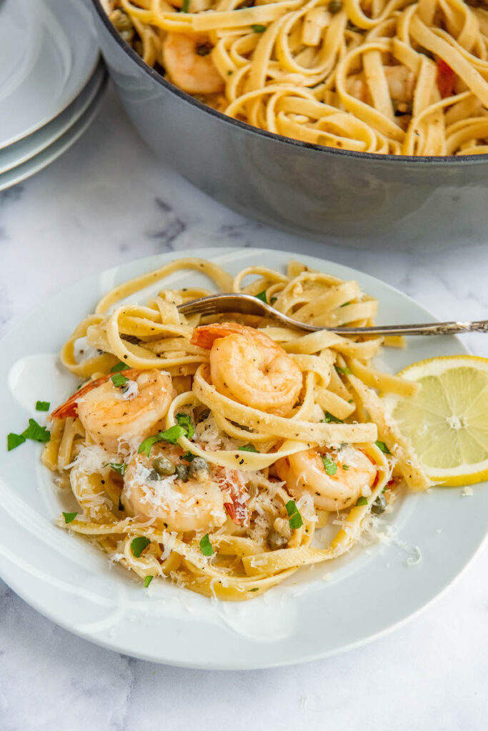 Shrimp Scampi with a slice of lemon on a plate with a fork.