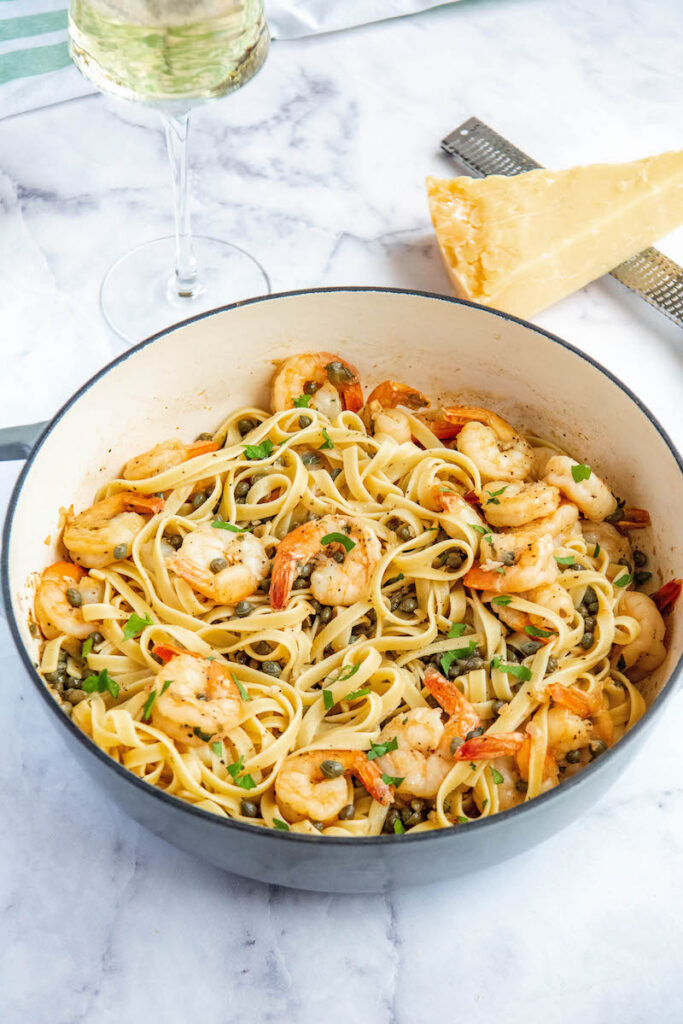 Shrimp Scampi in a pan tossed with pasta with a glass of wine.
