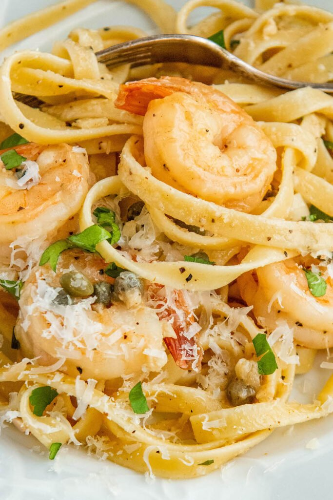Up close image of shrimp scampi pasta tossed together with parmseasn cheese.