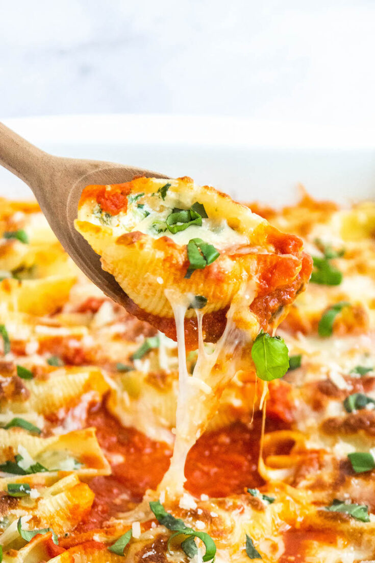 Stuffed shells with spinach being pulled out of casserole dish with wooden spoon.