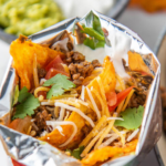 Pinterest image with wording on top of an up close photo of walking tacos in a bag.