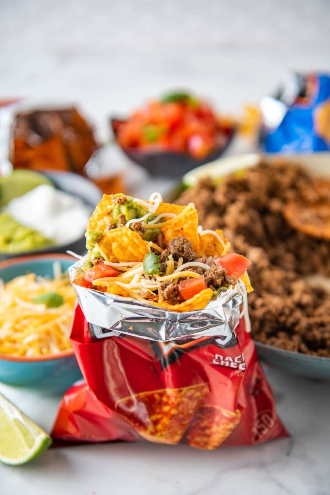 An open Dorito bag contains all the ingredients for walking tacos