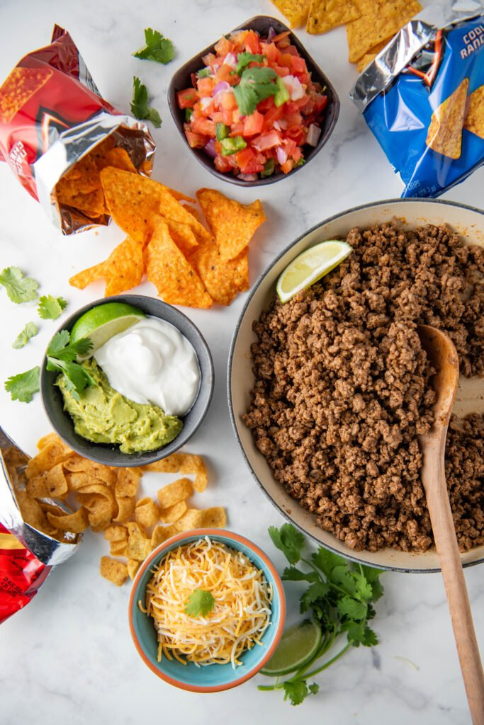 All ingredients for walking tacos are spread out on a white table