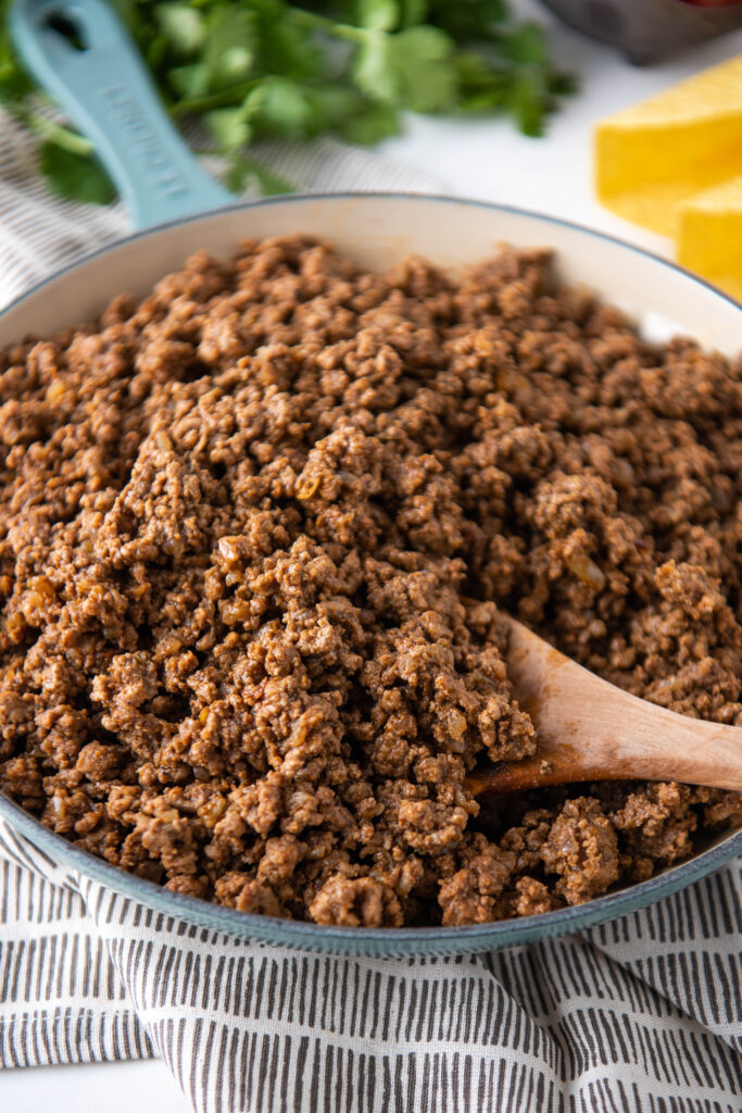 A pot of ground beef is being stirred with a wooden spoon