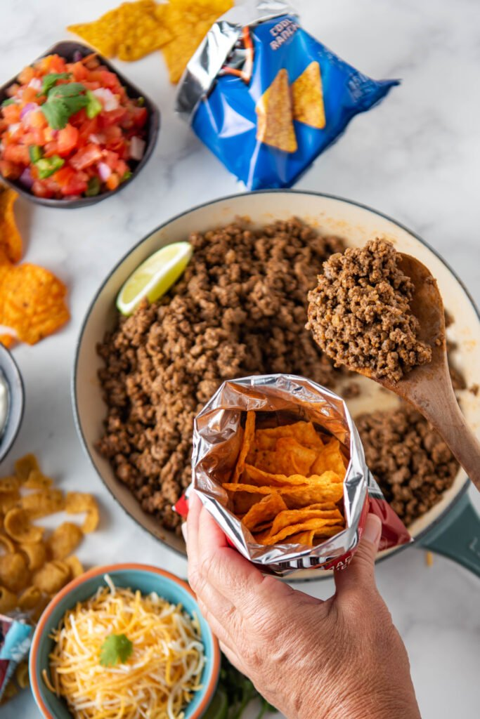 An open Dorito's bag is held over a pan full of ground beef
