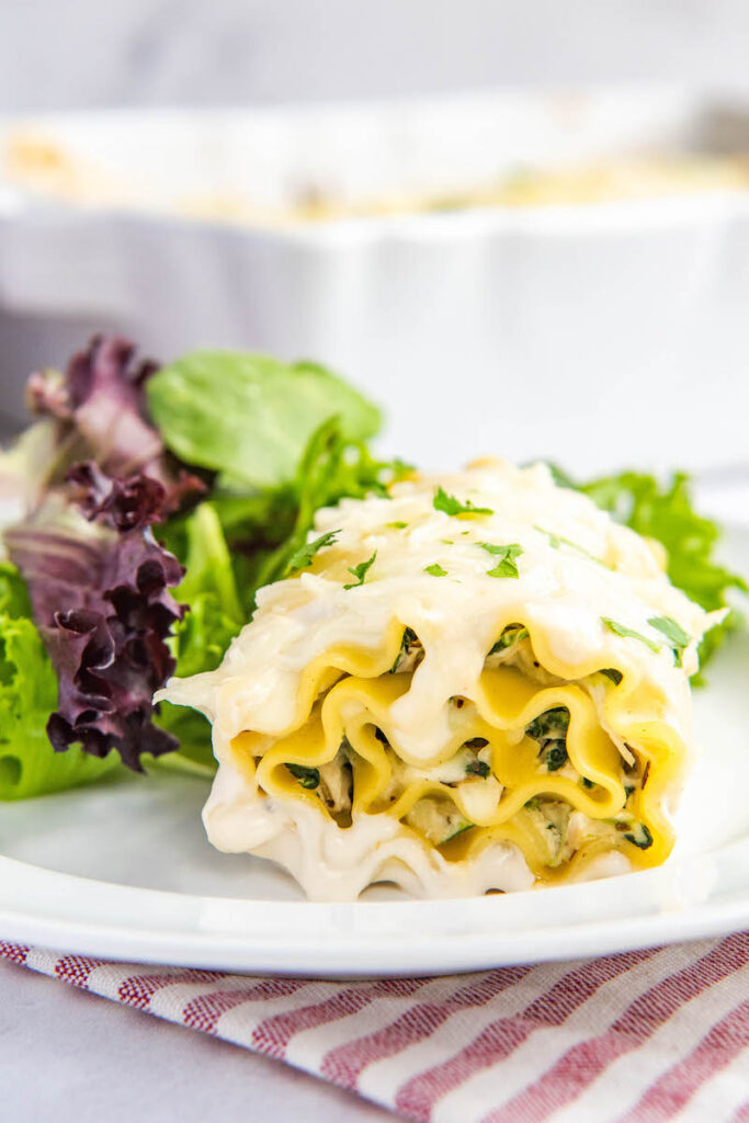 Chicken lasagna rollup sits on a white plate next to a leafy salad