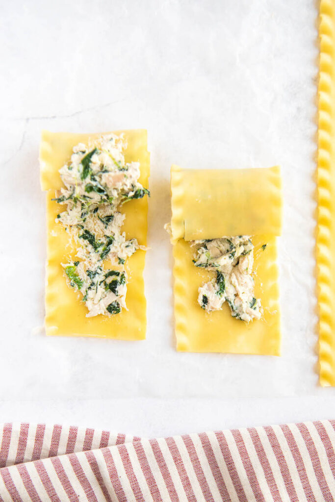 Lasagna noodles are being rolled up on a white surface