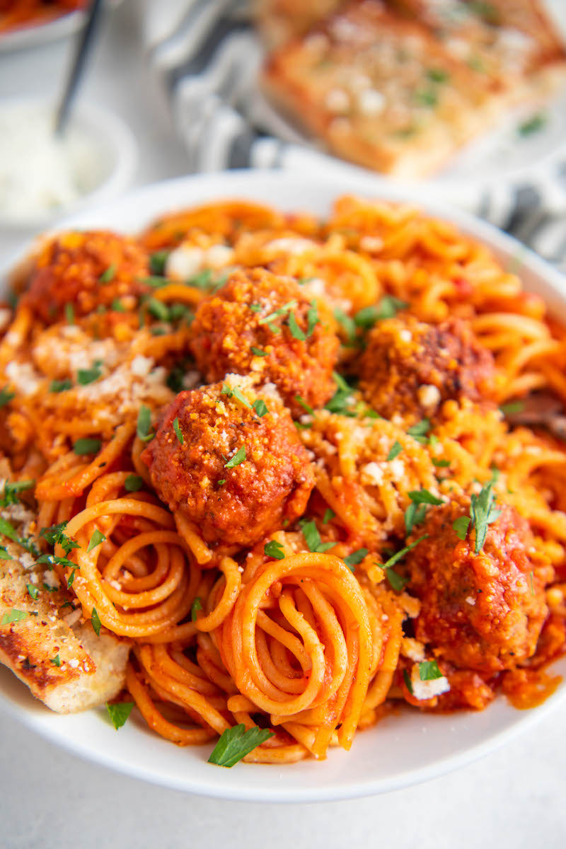 Instant Pot Spaghetti and Meatballs on a white plate with cheese and parsley on top.