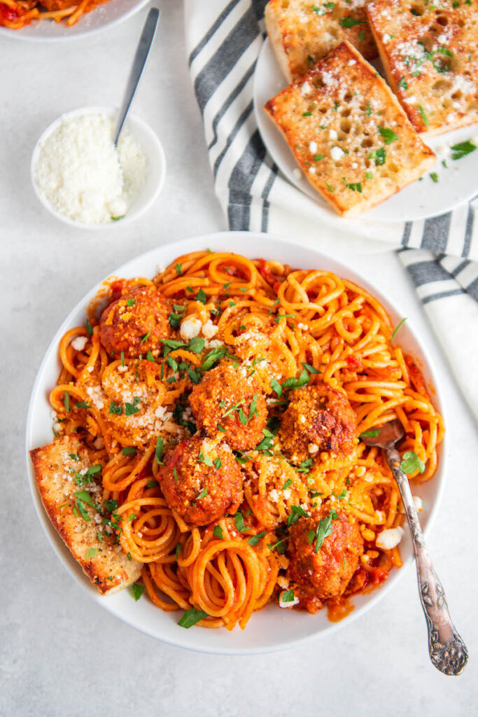 Overhead image of spaghetti and meatballs with a fork and garlic bread.