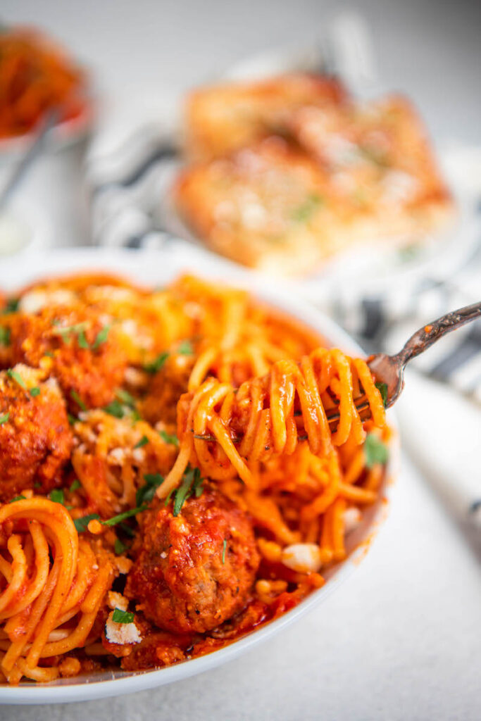 Up close image of spaghetti being twirled on a fork.