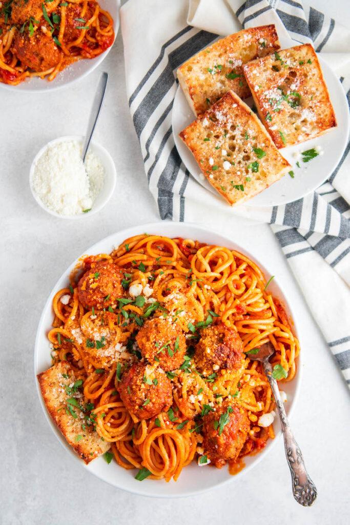 Overhead image of spaghetti and meatballs on a plate with a side plate of garlic bread and a bowl of parmesan cheese.