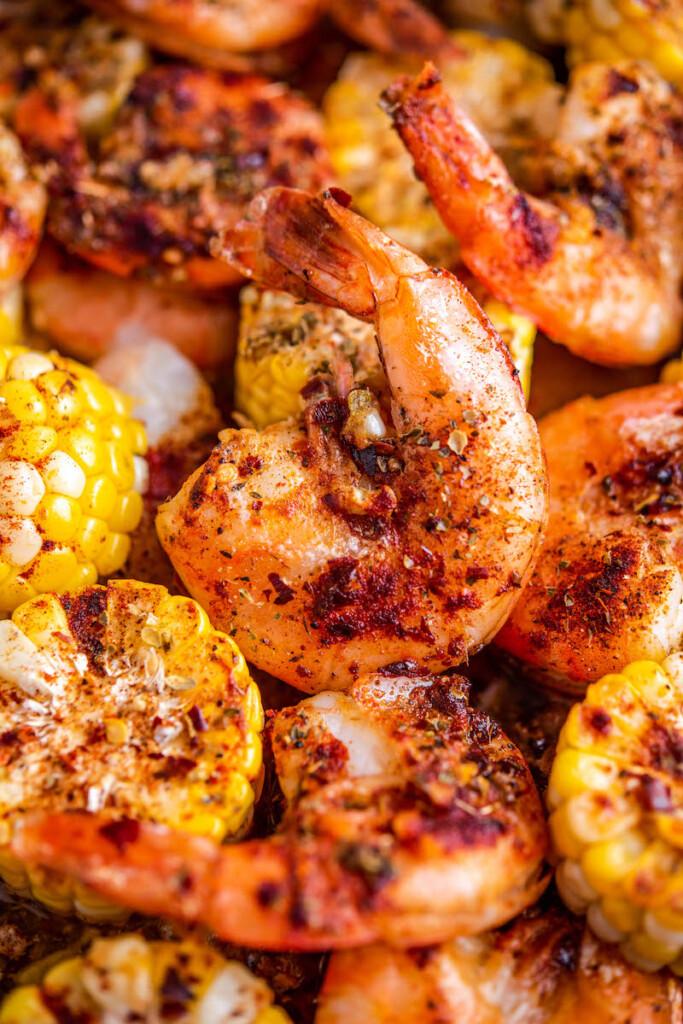 Garlic butter shrimp and corn on a roasting pan.