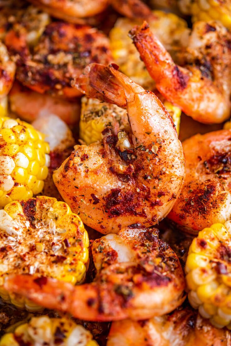 Cooked shrimp and corn on a roasting pan.