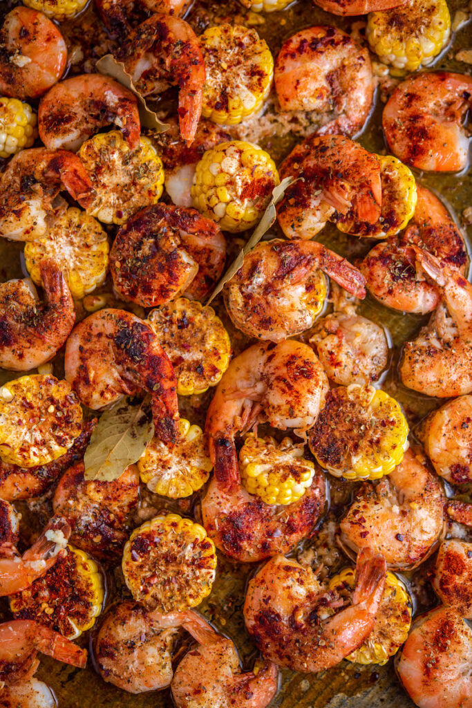 Cooked shrimp with corn in a roasting pan.