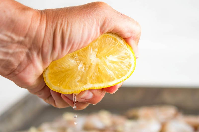 Lemon in a hand being squeezed with juice coming out.