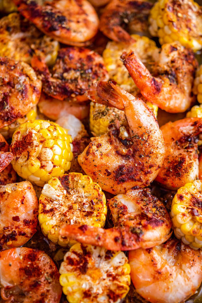 Garlic Butter Shrimp with corn and seasonings on a sheet pan.