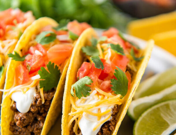 Hard shell tacos are on a white plate with sliced limes