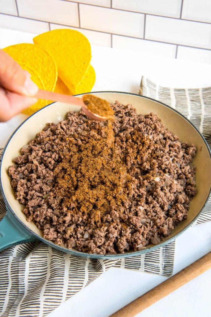 Homemade taco seasoning is being sprinkled into a skillet of ground beef