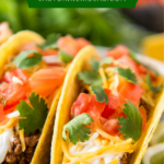 Up close image of ground taco meat in a crispy taco shell with toppings.