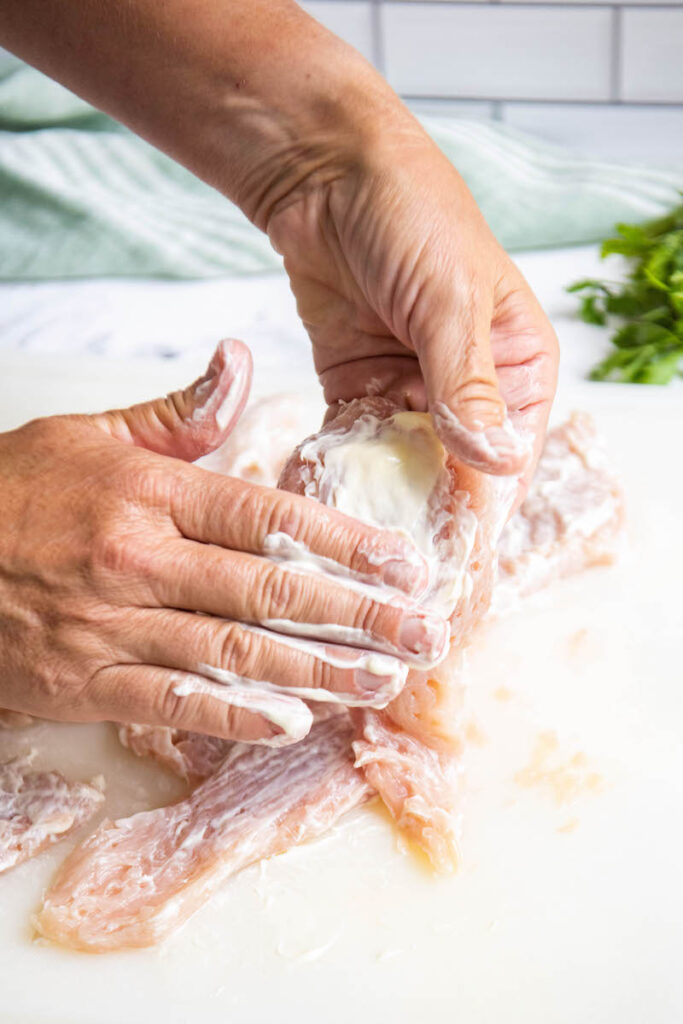 Thin chicken breasts on a cutting board being coated in mayo.