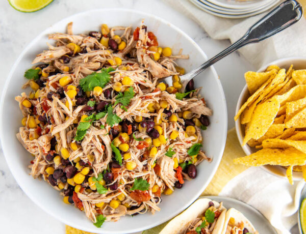 Crockpot Mexican Chicken in a bowl with a spoon and on plates in tacos with limes and tortilla chips.