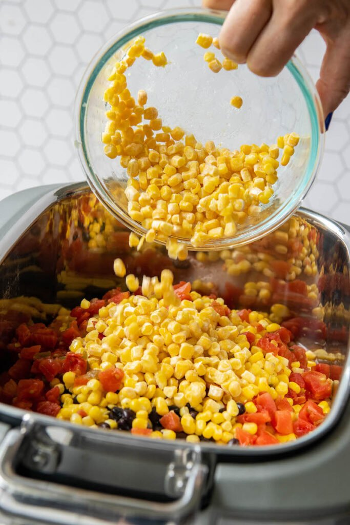 Corn being poured into a a crockpot with a glass bowl.