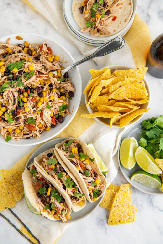 Overhead view of mexican chicken in tacos, in a bowl with a fork and cilantro and tortilla chips and lime wedges on a plate and napkin.