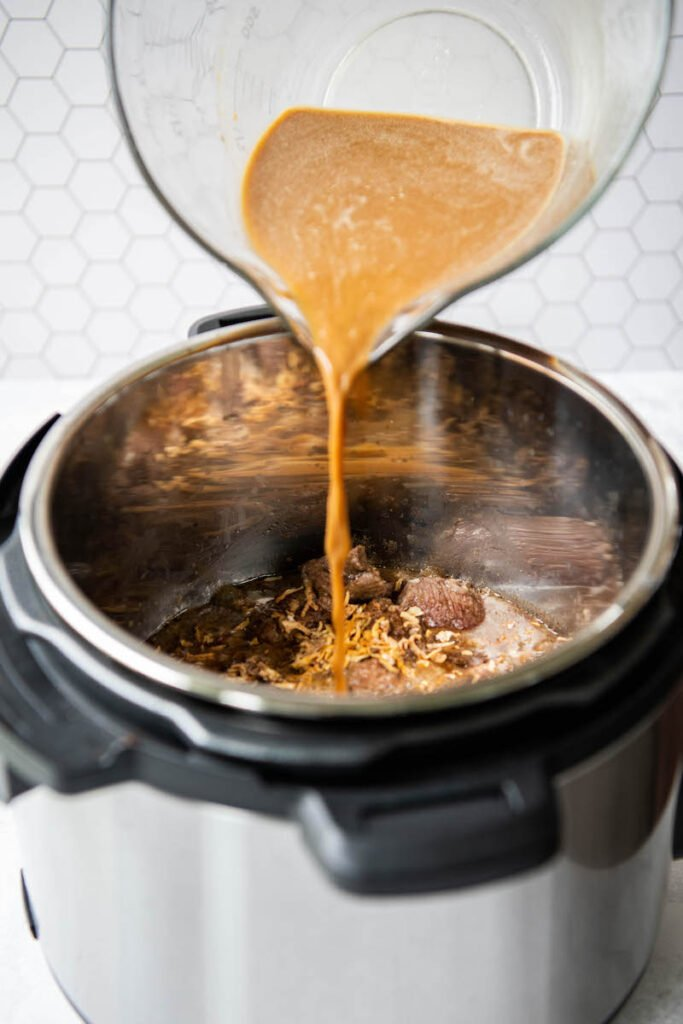 Brown gravy being poured into an instant pot.
