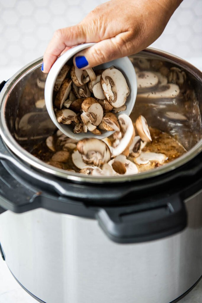 Sliced mushrooms being added to instant pot.