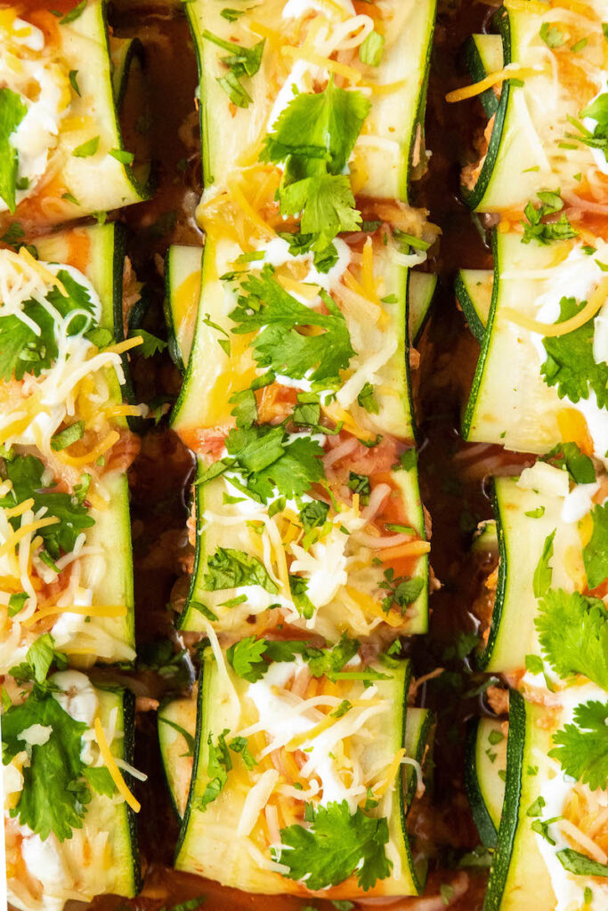 Zucchini enchiladas with cilantro and sour cream on top.