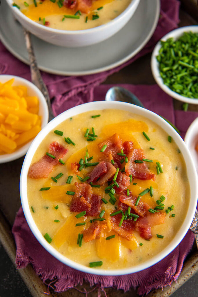 A bowl of potato soup is on a table with a red tablecloth