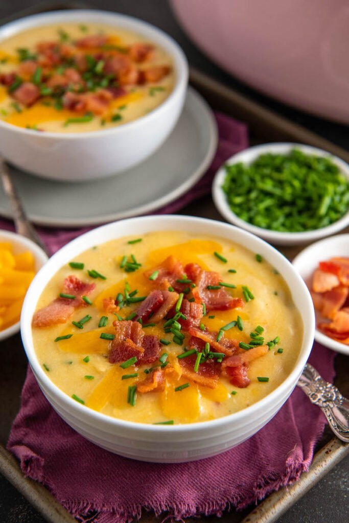 Two bowls of potato soup are on a table with a red tablecloth