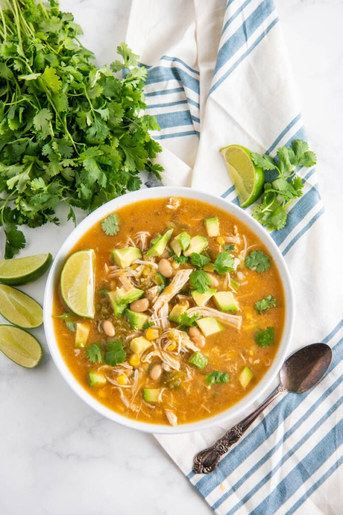 Overhead image of chicken crockpot soup with a napkin, spoon, cilantro, avocado and lime.