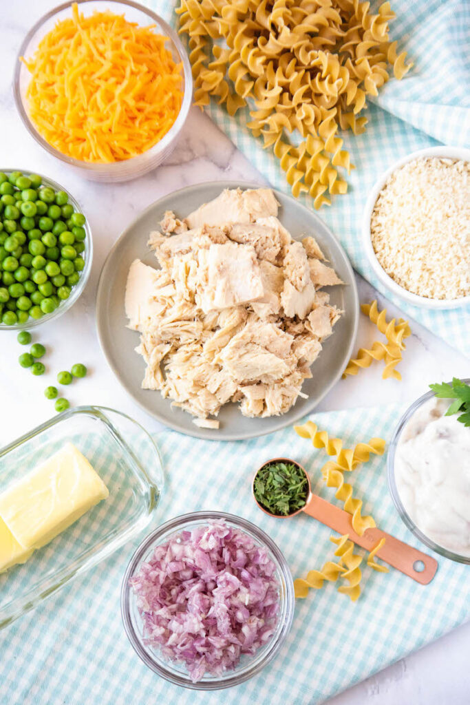 The ingredients for the tuna noodle casserole are separated on a white tabletop.