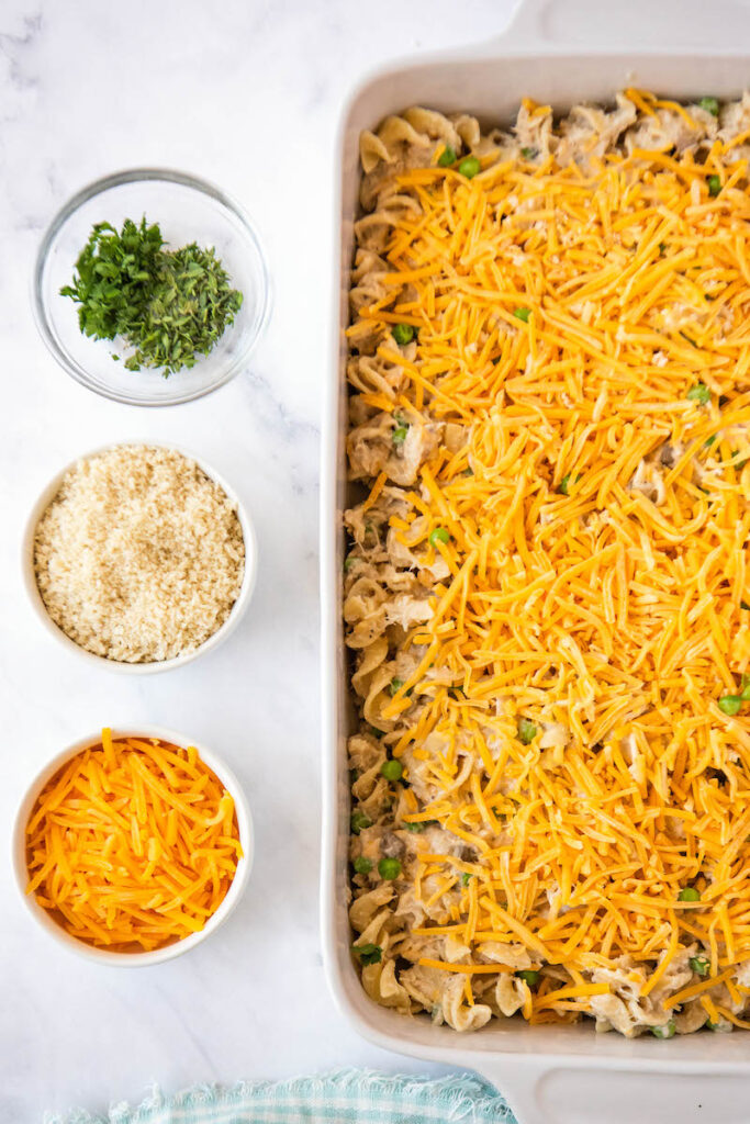 Uncooked tuna casserole is in a dish, covered with cheddar cheese.