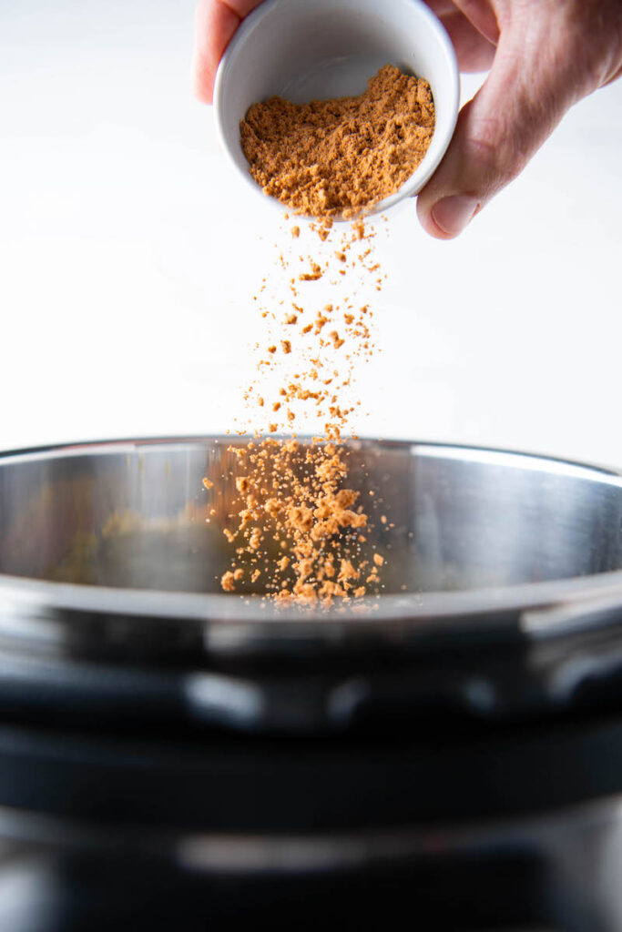 Taco seasoning is being sprinkled into the Instant Pot
