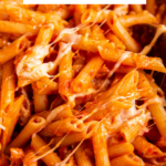 One pot penne pasta recipe in a pot with cheese on top with wording for pinterest.