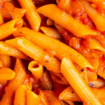 Up close image of pasta in red sauce in a pan with wording on top for pinterest.
