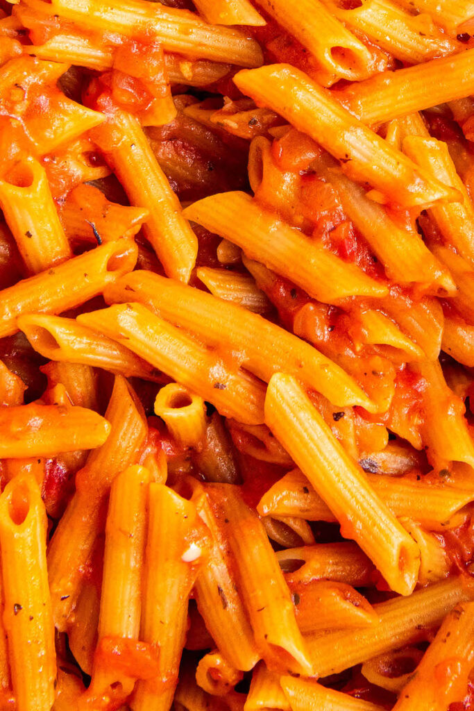 Pasta noodles are covered in delicious red sauce