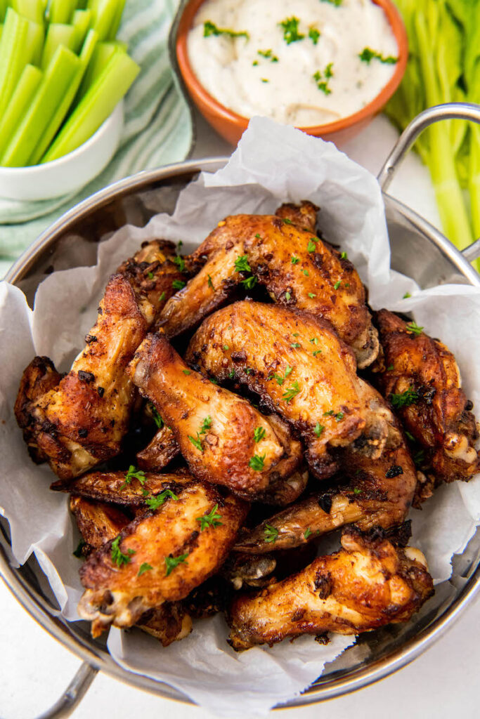 Several wings sit on a piece of parchment paper with celery and sauce in the background.