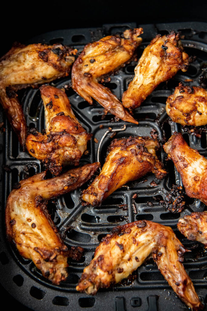 Cooked wings sit in the bottom of an air fryer.