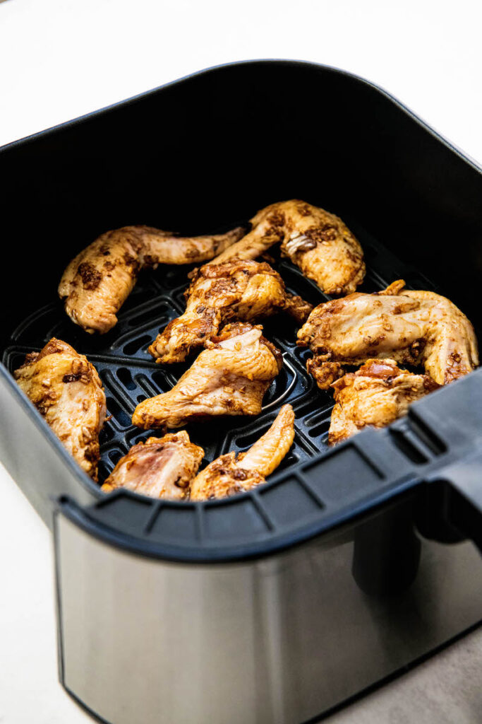Cooked chicken wings are in an air fryer.