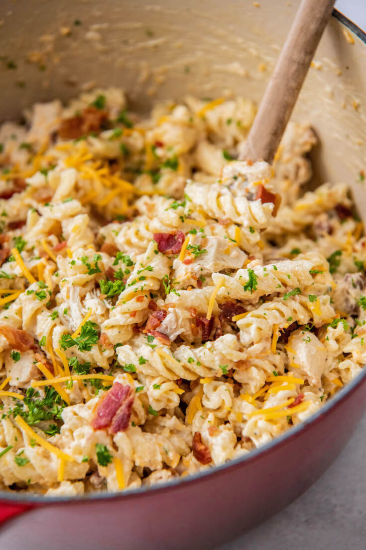 A large pot is filled with rotini noodles, bacon, and sauce.